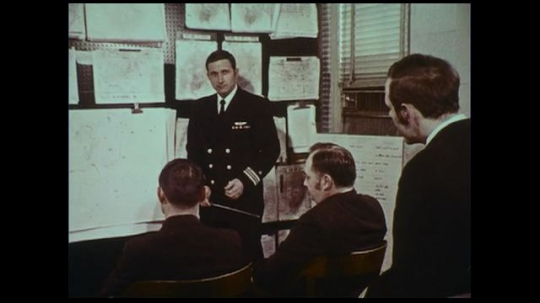UNITED STATES 1970s: Naval officers discuss analysis as another naval officer at the weather central observes the computer data.