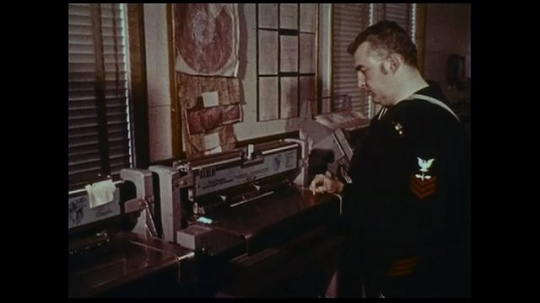 UNITED STATES 1970s: A naval officer awaits the printing of faxed weather information while another observes as a computer automatically prints weather data.