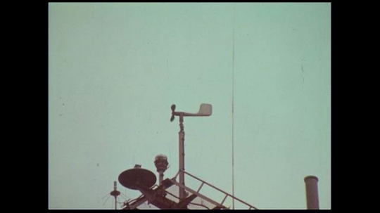 UNITED STATES 1970s: A vane sits atop the deck of a ship as windows turn it.