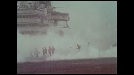 UNITED STATES 1970s: A naval officer releases a white balloon into the air as the ship deck turns white from the smoke of the planes taking off.