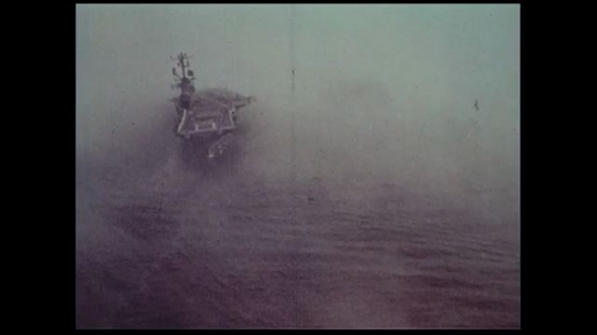 UNITED STATES 1970s: A ship captain makes a radio announcement as a foggy mist surrounds his war ship at sea.
