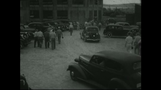 UNITED STATES: 1940s: Cars and people arrive at mine. Cable and tower at mine. Men wait to go down mine.