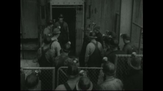 UNITED STATES: 1940s: Miners enter mine shaft lift. Miner closes gate for mine shaft cage. Miners enter mine from cage. Miners carry lunch boxes.