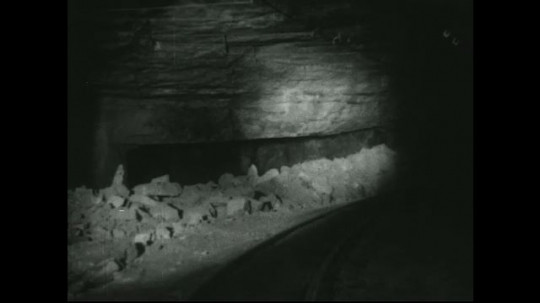 UNITED STATES: 1940s: View of rubble next to mine shaft track. Trolley wires inside mine shaft.