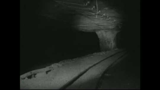 UNITED STATES: 1940s: View of train tracks inside mine shaft.