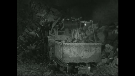 UNITED STATES: 1940s: Mine machine scoops up rock and transfers it to cart.