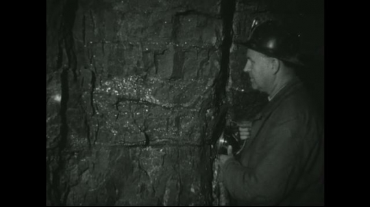 UNITED STATES: 1940s: Miner shines torch on ore in rock. Miner points finger at vein of ore in rock face.