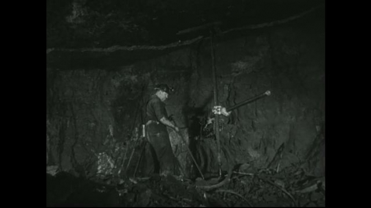 UNITED STATES: 1940s: Miner prepares metal pole in mine shaft. Drill bores through rock. Dust and water from drill hole in rock.