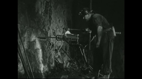 UNITED STATES: 1940s: Miner sets up small drill in underground shaft.