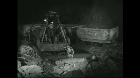 UNITED STATES: 1940s: Miner scoops up loose rock with digger view from side. Miner uses machine to move rock from floor to cart.