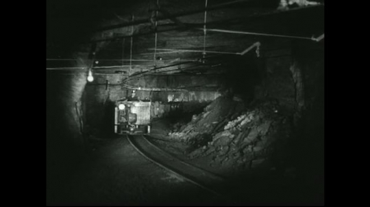 UNITED STATES: 1940s: front view of train travel through mine shaft. Man drives train underground. Carts loaded with rocks