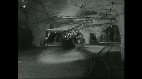 UNITED STATES: 1940s: Mine shaft train stops to pick up miner. Trains pass each other in mine.