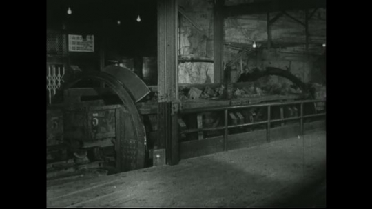 UNITED STATES: 1940s: Machine turns carts on train track. Rock tipped from carts.
