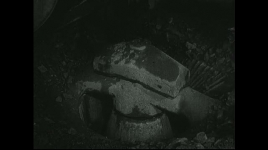 UNITED STATES: 1940s: Machine dry crushes ore from mine. Rock falls into machine.