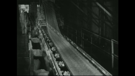 UNITED STATES: 1940s: Ore travels on conveyor belt. Machine separates ore from lead.