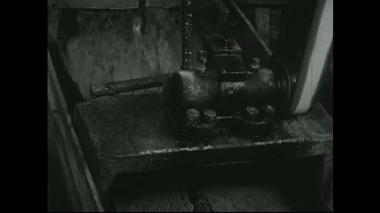 UNITED STATES: 1940s: Ore pulp passes over screens in mill machine.