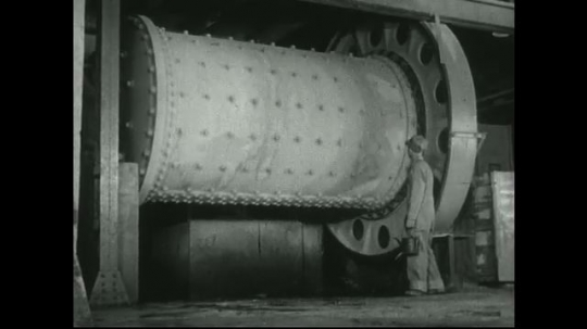UNITED STATES: 1940s: Man walks past machine in lead mill. Machine separates ore from pulp.  Water in grinding machine