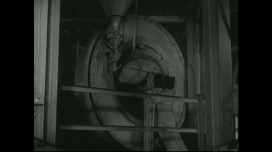 UNITED STATES: 1940s: man in mill building inspects rotating machine.