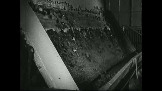 UNITED STATES: 1940s: lead sediment drops onto conveyor from filter machine.