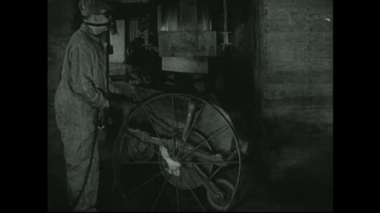 UNITED STATES: 1940s: man watches as powder residue falls into cart from machine. Mechanical loader distributes residue.