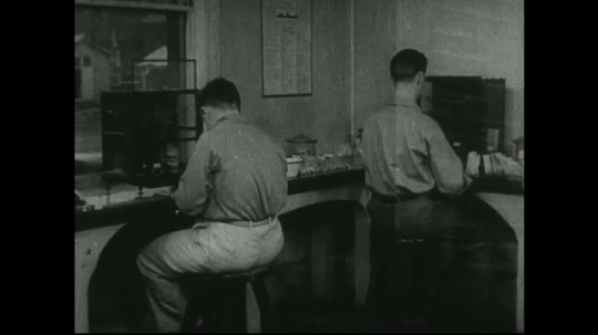 UNITED STATES: 1940s: Men test lead samples in lab. Man unloads grain from train carriage.
