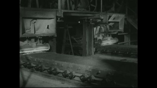 UNITED STATES: 1940s: Factory worker walks to machine and adjusts dial. Residue and flames on flat surface of machine