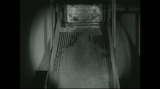 UNITED STATES: 1940s: Residue drops down chute with metal grid. Dust as residue falls through machinery.