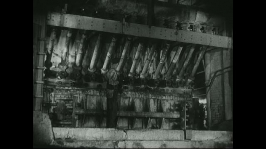 UNITED STATES: 1940s: factory worker clears oxygen inlet in blast furnace.