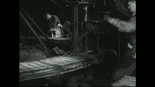 UNITED STATES: 1940s: man pushes and pulls machine into place over metal. Stamp made on metal.