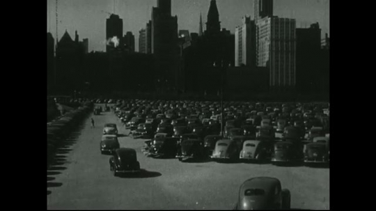 UNITED STATES: 1940s: cars arrive in car park by city. New cars in car park.
