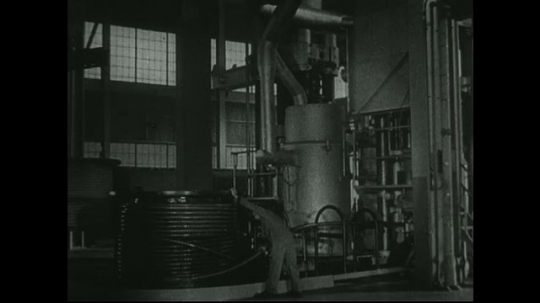 UNITED STATES: 1940s: Man works in engine room. Close up of machine in room. View across valley towards mine.