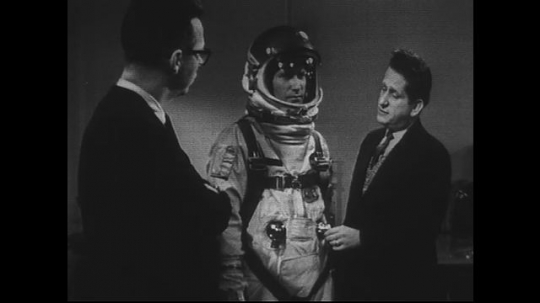 UNITED STATES 1960s: Two men stand with model in space suit, man describes suit features.