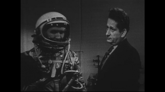 UNITED STATES 1960s: Man models space suit, zoom out to men discussing suit.