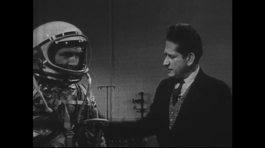 UNITED STATES 1960s: Man models space suit, man describes features of suit.