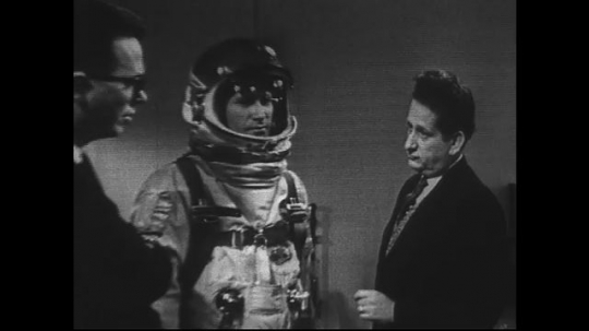 UNITED STATES 1960s: Zoom out, two men on set with model in space suit.
