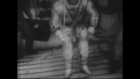 UNITED STATES 1960s: Astronaut in space suit trains in moon gravity simulator.