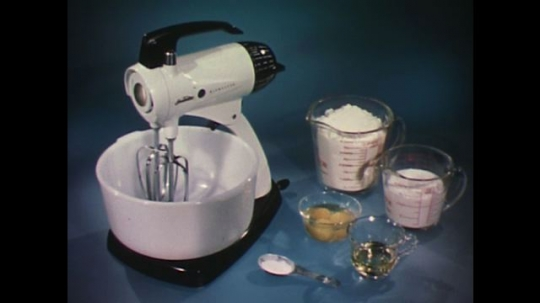 UNITED STATES 1960s: Ingredients next to electric mixer, hand pours flour in bowl.