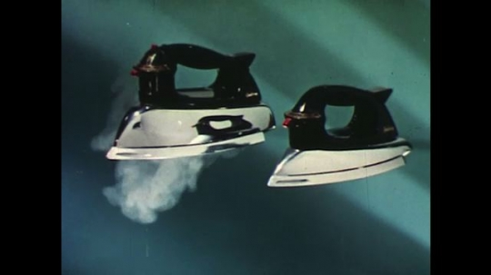 UNITED STATES 1960s: Two irons side by side, one steaming.