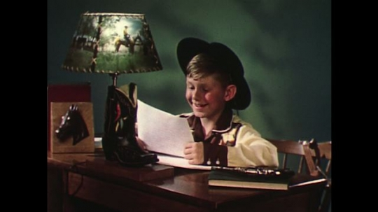 UNITED STATES 1960s: Boy in cowboy outfit reads letter at desk.