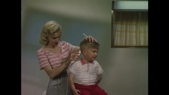 UNITED STATES 1960s: Woman cuts son