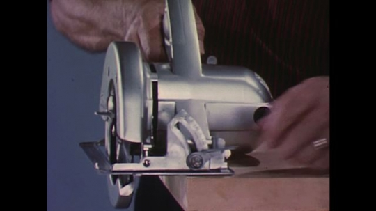 UNITED STATES 1960s: Hands adjust angle on circular saw / Saw cuts at angle towards camera.