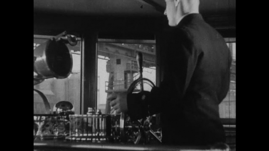 UNITED STATES 1930s-1940s : A helmsman turns a helm to steer a ship. A plant operator spins a helm to operate a generator.