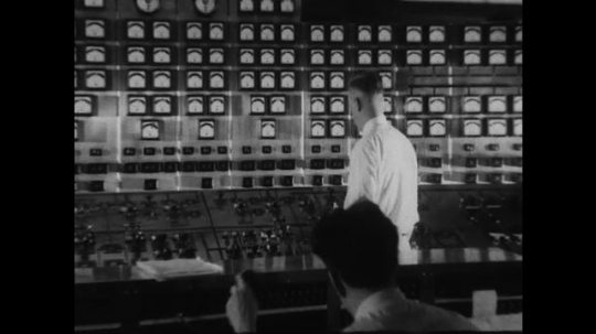 UNITED STATES 1930s-1940s : A switchboard operator checks the display on his switchboard. An extreme long aerial shot of the River Rouge power plant.