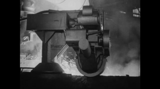 UNITED STATES 1930s-1940s : A machine arm moves and then dips into a vat of molten iron.