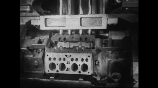 UNITED STATES 1930s-1940s : A drilling machine drills holes in the top of a v8 engine block.