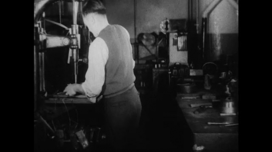 UNITED STATES 1930s-1940s : A scientist works in a factory laboratory doing quality tests on newly cast machine parts. Another scientist weighs material on a scale.