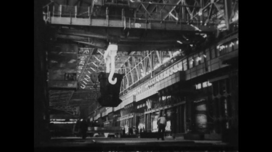 UNITED STATES 1930s-1940s : An open container, carrying molten iron, moves across a factory floor on a hanging track. The iron is then poured into a channel that funnels the iron into a furnace.