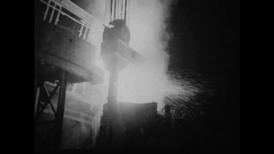 UNITED STATES 1930s-1940s : A tapped electric furnace pours tons of molten metal into a large open container.