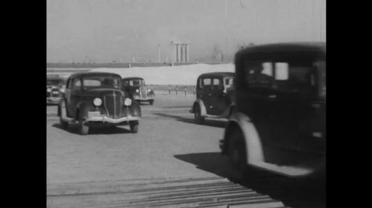 UNITED STATES 1930s-1940s : Cars drive into and out of a Henry factory property. Workers labor in a field on the factory grounds.