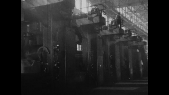 UNITED STATES 1930s-1940s : A medium shot of a factory floor with large machines. Long sheets of rolled-out ingots are cooled with water.